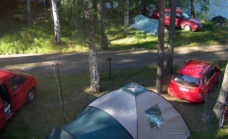 Telttoja, autoja ja antenneita järven rannalla.