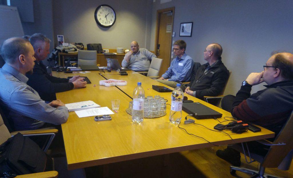 Toimikunnan jäseniä pöydän ympärillä.