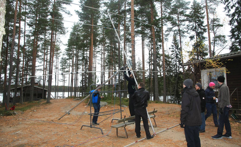 Leirin osallistujat nostavat pikkumastoa, jonka päässä on yagi-antenni