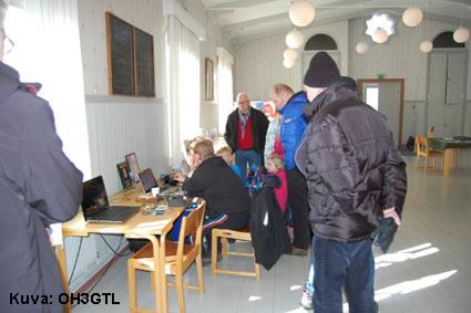 Yleisö seuraa yhteydenpitoa radioamatööriasemalla.