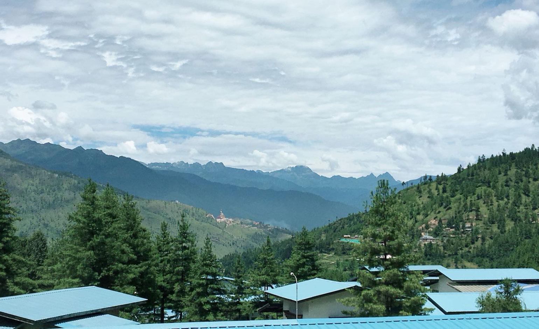 Himalajan vuoristo pilvipeitteessä, syvänvihreää havumetsää ja vaaleanvihreitä rakennusten kattoja.