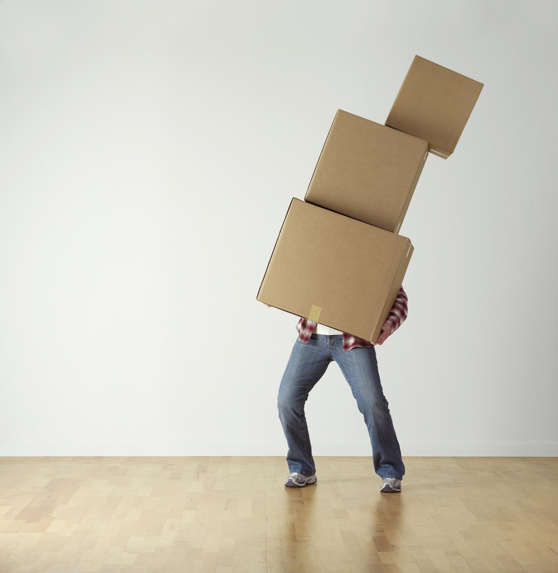 Mies kantaa laatikoita.
