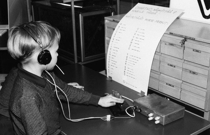 Poika lukee lapulta morseaakkosia ja opettelee sähkötystä.